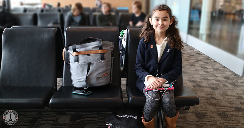 photos of daughter at airport sitting on chair with bags on our way to Montreal