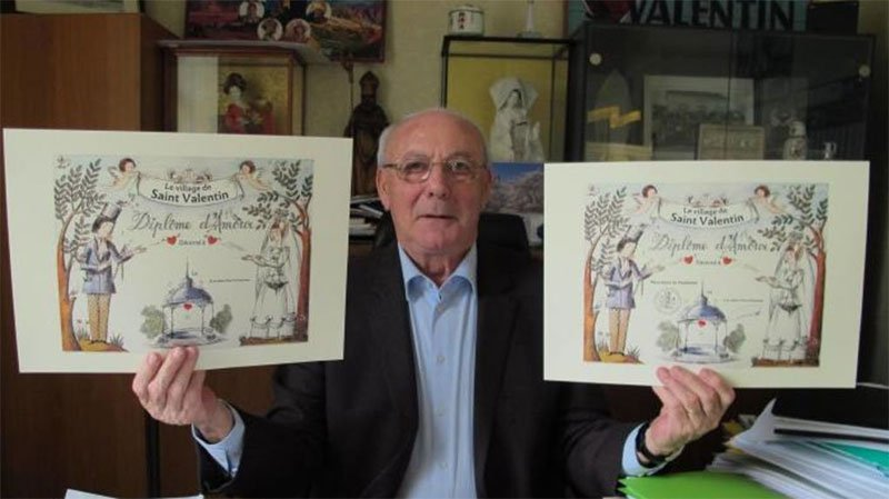 The mayor of Saint-Valentin poses with two lovers certificates which he gives to couples