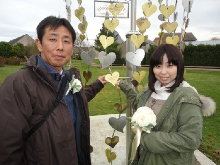 A Japanese couple posing at the tree of hearts in Saint-Valentin
