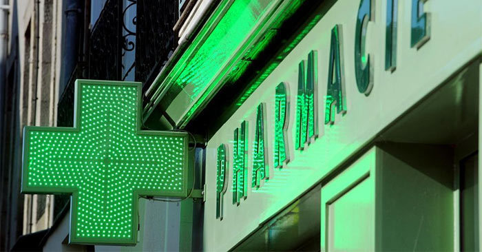 Green pharmacie sign with cross in France