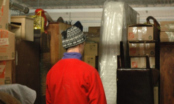 Blake in the storage unit looking at all of our stuff