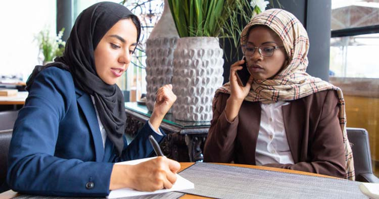 two woman wearing a hijab at the office