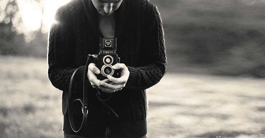black and white picture holding vintage camera