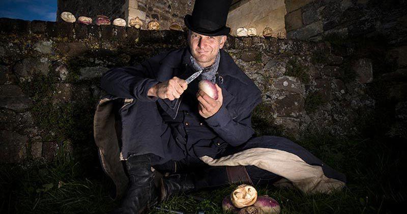 Man carving a turnip jack o'lantern