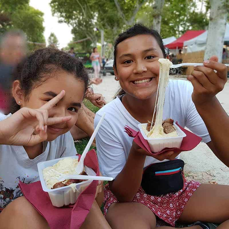 Photo of daughter and cousin eating Aligot at a fair in Montpellier