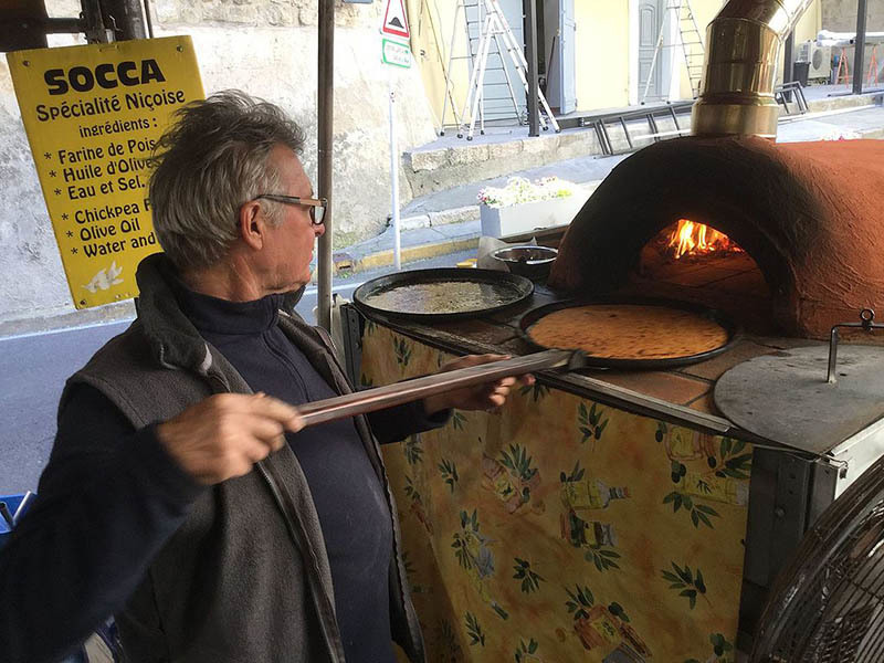 photo of vendor cooking Socca, a traditional niçoise dish from nice France