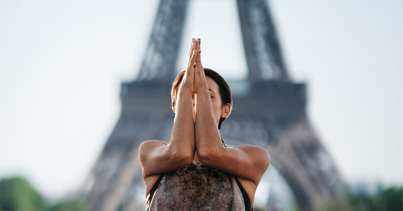 Girl standing in front of Eiffel tower performing a yoga pose