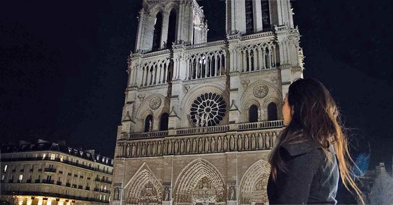Annie Andre standing in front of Eglise de Notre Dame De Paris:
